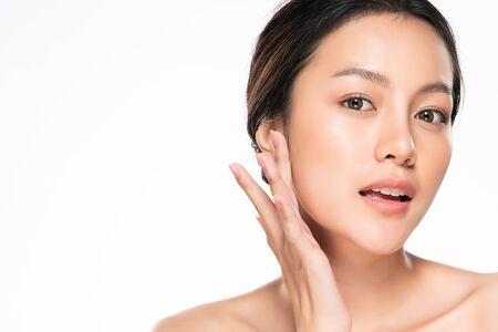 Foto de Beautiful Young Asian Woman with Clean Fresh Skin touch own face - Imagen libre de derechos