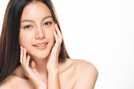 Foto de Beautiful Young Asian Woman with Clean Fresh Skin is touching her face - Imagen libre de derechos