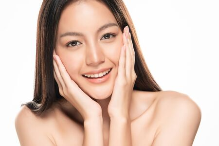 Photo for Beautiful young Asian woman touching soft cheek and smile with clean and fresh skin. Happiness and cheerful with, isolated on white background, Beauty and Cosmetics Concept, - Royalty Free Image