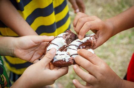 Photo pour Children sharing a doughnut. - image libre de droit
