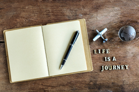 Diary on wooden background with word Life is a journey