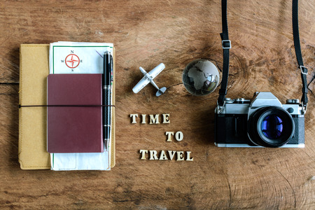Foto de Notebook with map, passport and camera on wooden background with word Time to travel - Imagen libre de derechos