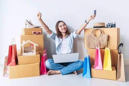 Photo pour Happy young asian woman with colorful shopping bag, fashion items and stack of cardboard boxes at home, Using credit card for online shopping concept - image libre de droit