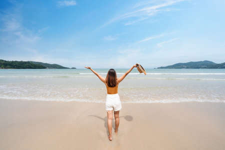 Photo for Young woman traveler relaxing and enjoying at beautiful tropical white sand beach with wave foam and transparent sea, Summer vacation and Travel concept - Royalty Free Image