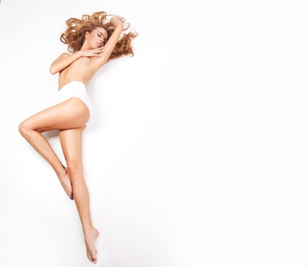 Delicate blond woman lying on a white background