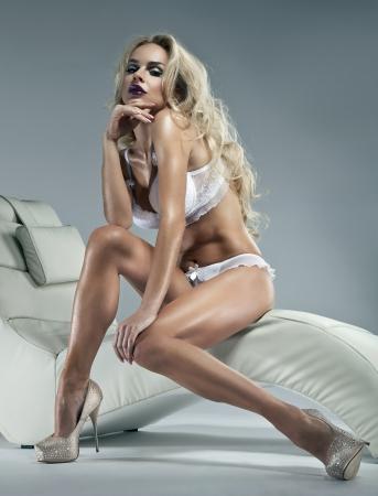 Foto de Sexy blonde woman with winter makeup sitting on a stylish chair  - Imagen libre de derechos