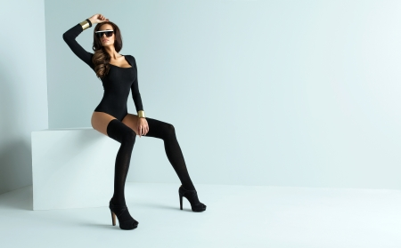 Sexy woman wearing sunglasses and black stockings