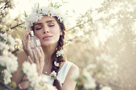 Beautiful sensual woman dreaming with perfume bottle in hands