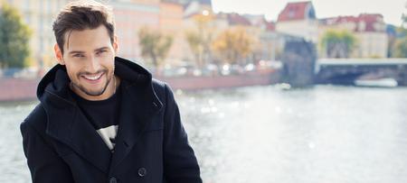 Photo pour Paronamic photo with handsome smiling man in coat - image libre de droit