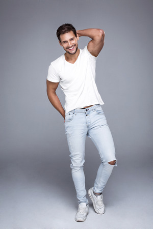 Foto de Handsome smiling man wearing jeans and white t-shirt. Pure natural photo of natural man with perfect smile - Imagen libre de derechos