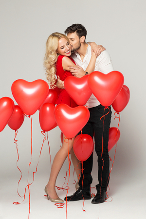 Foto de Kissing couple posing on grey background with balloons heart. Valentine's day. - Imagen libre de derechos