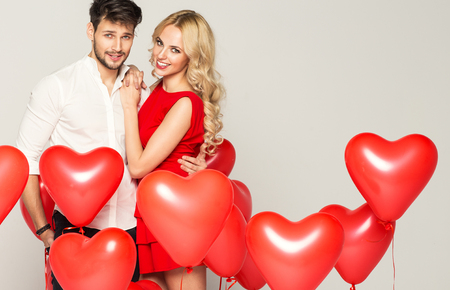 Foto de Portrait of cute couple with balloons heart - Imagen libre de derechos