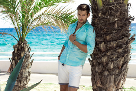Foto de Handsome model in turquoise shirt posing in summer scenery - Imagen libre de derechos