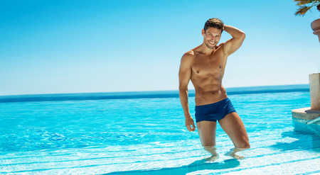 Summer photo of muscular smiling man in swiming pool