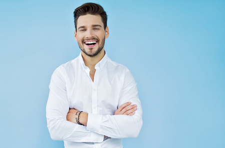 Photo pour Sexy smiling handsome man with crossed arms - image libre de droit
