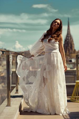 Foto de Beautiful bride in white dress posing outdoor over city view - Imagen libre de derechos