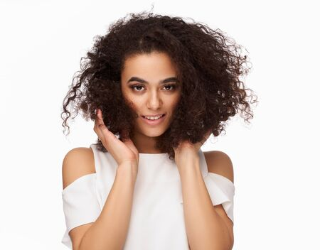 Photo pour Portrait of beautiful latin american woman touching her afro hairstyle isolated on white background - image libre de droit
