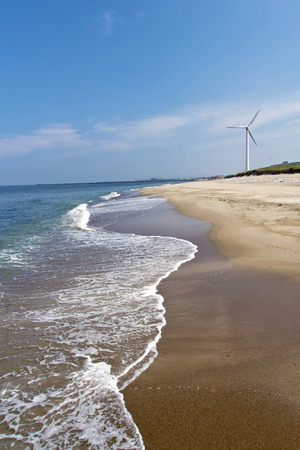 Energy Park - An agricultural field with wind turbines at the beach