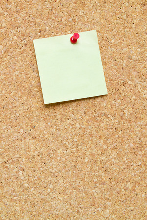 blank post it note pinned to a cork board  bulletin board