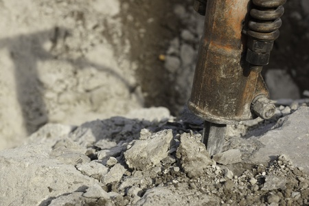 jack hammer used for breaking, chipping, and demolishing concrete close-up of bit with crushed concrete and shadow