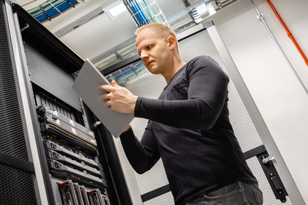 Photo pour Male Technician Using Digital Tablet In Datacenter to Monitor SAN and Servers - image libre de droit