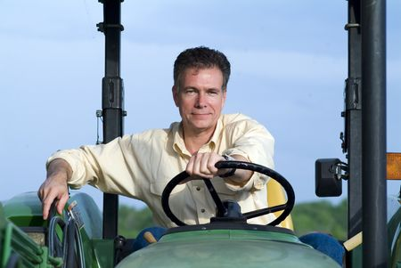 Handsome mature white male sitting comfortably on a big green tractor smiling contentedly and confidently.