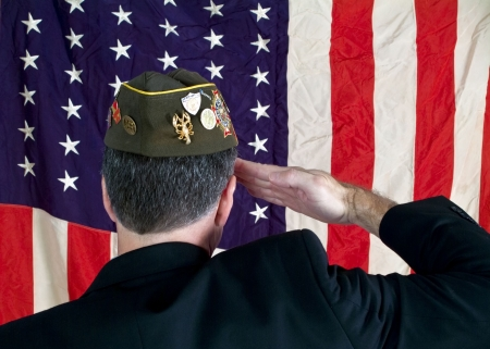 Foto per A Veteran wearing a decorated cap, saluting the American Flag. - Immagine Royalty Free