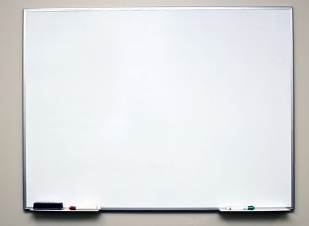 Clean dry erase board on a off white wall with markers in the tray