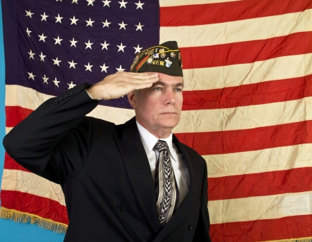 Foto per A man in a VFW cap saluting and standing in front of an old faded 48 star American flag.  - Immagine Royalty Free