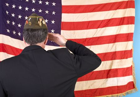 Foto per A man in a VFW cap saluting an old faded 48 star American flag.  - Immagine Royalty Free