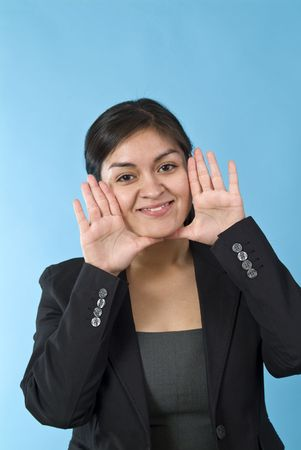 A young woman with her hands up to her face as if ready to call out to someone.