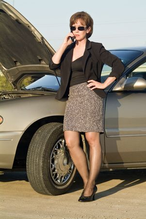 A woman on a cell phone next to a car that appears to be out of service.