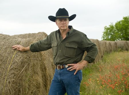A man standing by a row of large round bales of hay.