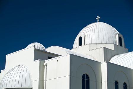 A domed Christian church whose stark white color contrasts sharply wih the dark blue sky.