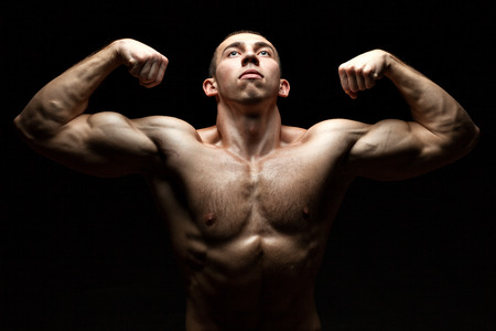 Portrait of a bodybuilder who build muscle and shows us at the same time looking up on black background.