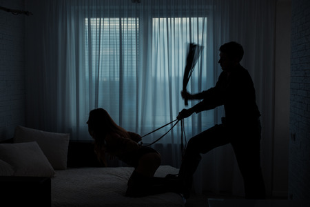 Black contours silhouette.  Man beats a woman with a whip in a dark room on the bed.