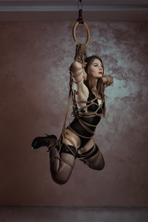 Girl tied with rope weighs suspended. Art shibari bondage.