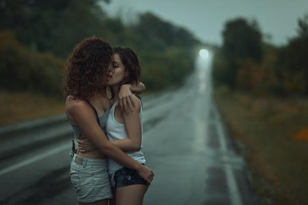 Girls lesbians kissing under the heavy rain. They got wet.