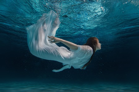 Photo for Woman in white dress swimming under water like a mermaid amid bursts. - Royalty Free Image