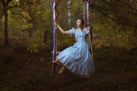 Girl swinging on a swing in the woods, her vintage retro dress.