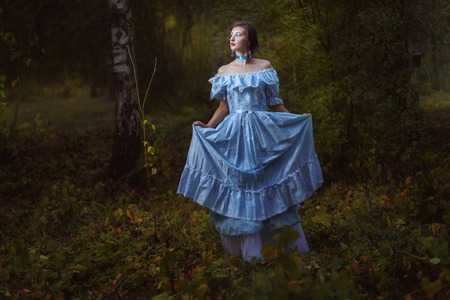 Girl in vintage dress in the forest at night.