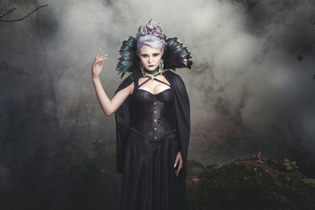 Beautiful woman conjures witch in the woods around the smoke.
