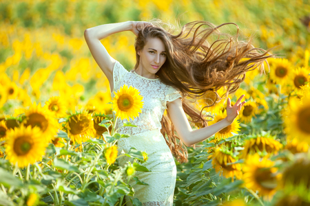 In the field with sunflowers is a woman, her long hair fluttering.