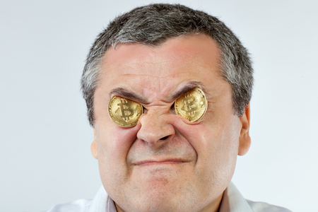 Portrait of a young man with bitcoin coins in his eyes.