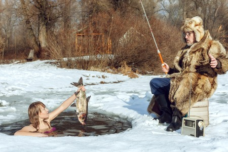 Foto de Young girl emerged from the ice-hole and stretches the fish to an elderly fisherman. - Imagen libre de derechos