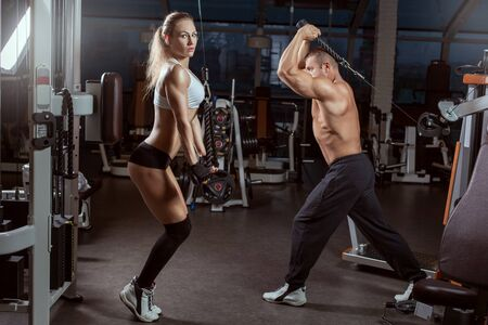 Photo for Man and woman athletes perform exercises on simulators in the gym. - Royalty Free Image