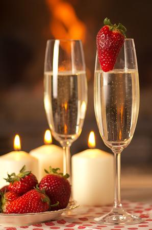 Foto de Champagne, strawberries and candles for a romantic evening. - Imagen libre de derechos