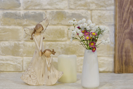 wooden statuette of mother and daughter, white candle, vase with wildflowers
