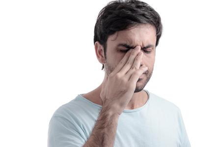 Sinus pain, sinus pressure, sinusitis. Sad man holding his nose because sinus pain