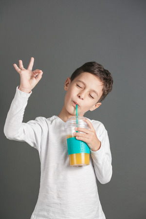 Little funny boy drinking a fresh cola juice through a strawの写真素材